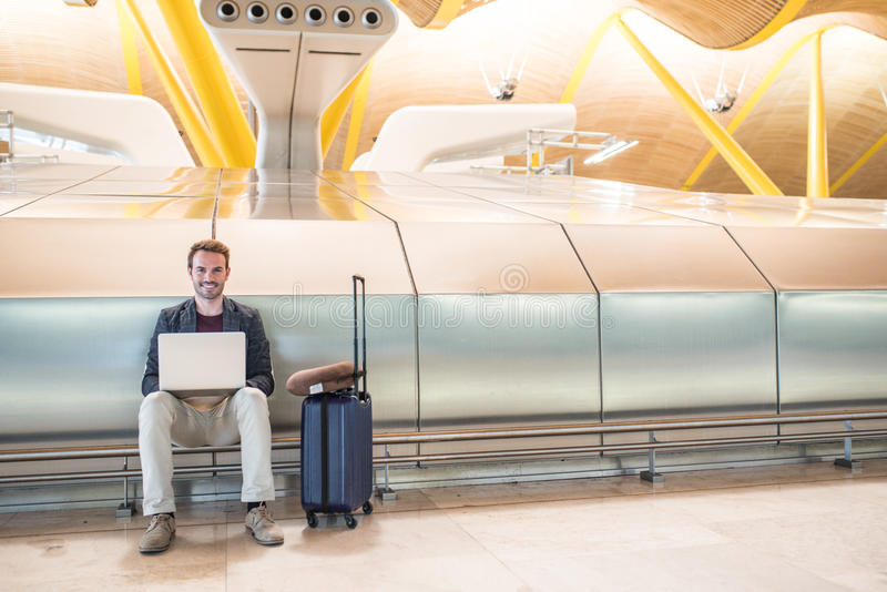 Young attractive man sitting at the airport working with a laptop waiting his flight with a suitcase stock image