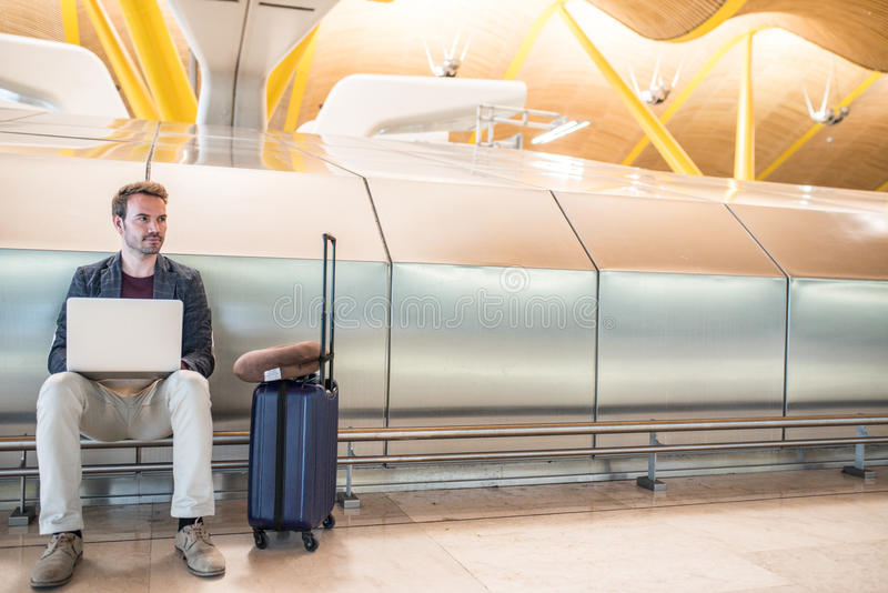 Young attractive man sitting at the airport working with a laptop waiting his flight with a suitcase stock photo