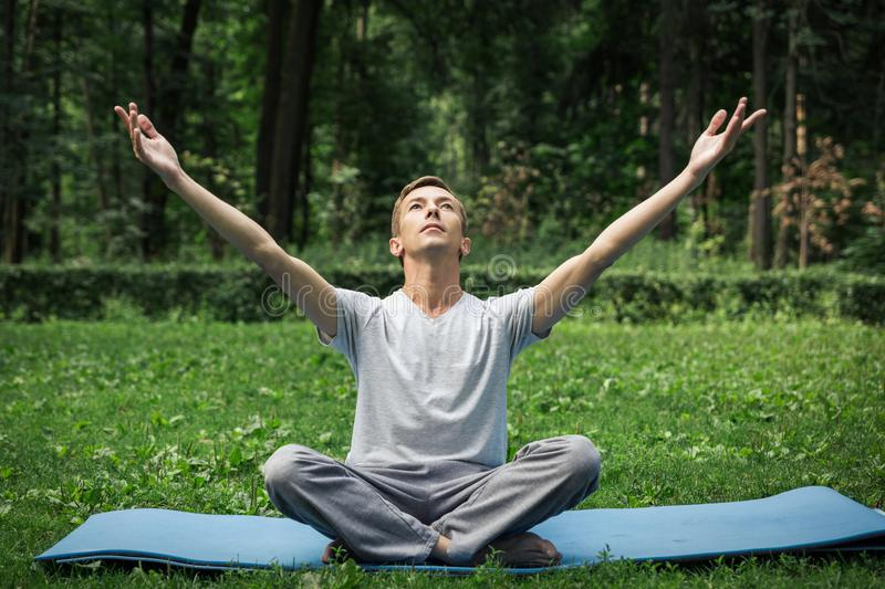 Young attractive man in sport clothes is meditating in the lotus position with a pacified face in the park against the background stock photography