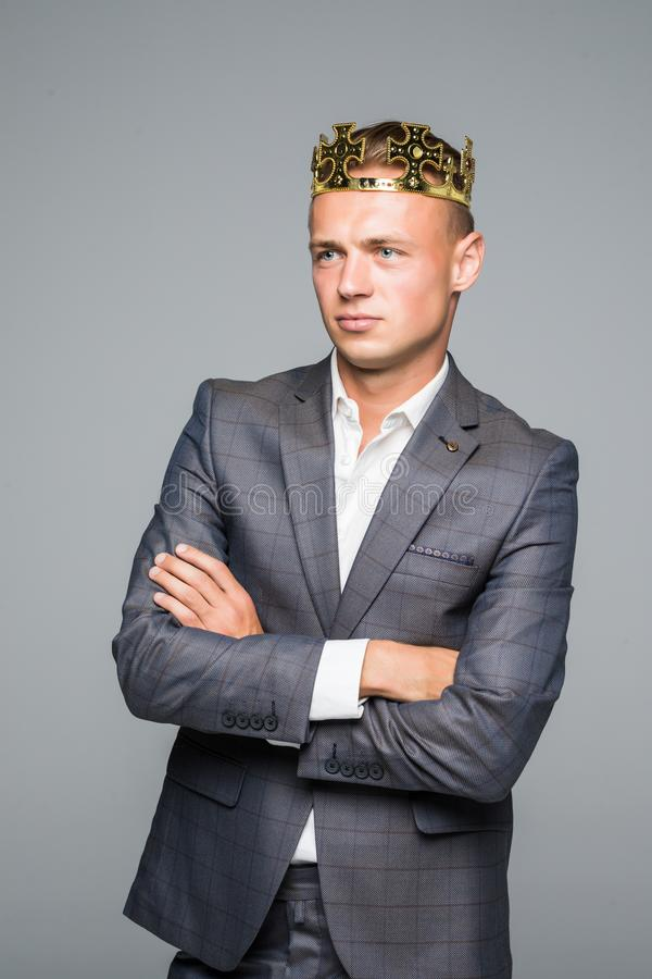 Young attractive man in suit holding above his head a golden crown on a gray background stock photo