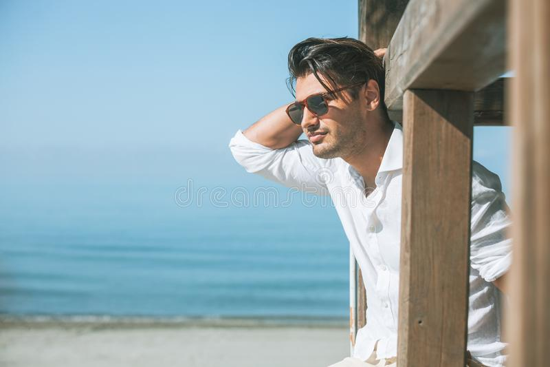 Young attractive man with sunglasses looking out over the sea during the summer. royalty free stock photography
