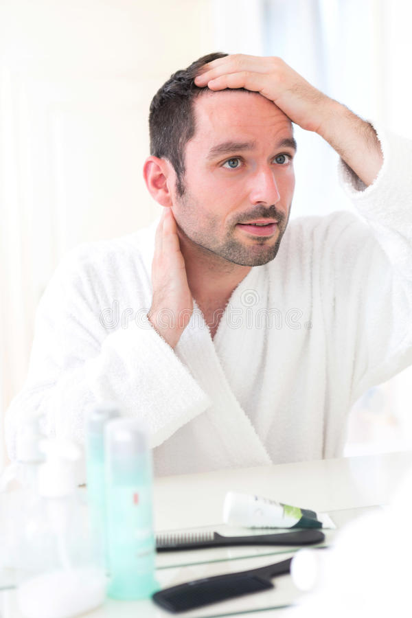 Young attractive man taking care of his hair royalty free stock photography