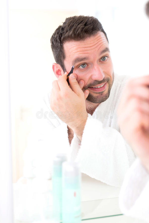 Young attractive man tweezing his eyebrow royalty free stock images