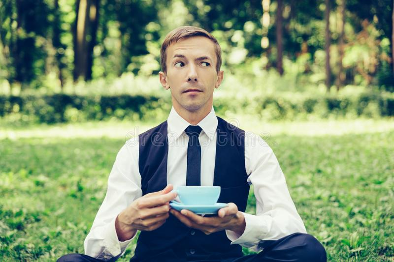 Young attractive man in a vest and tie resting on the nature and drinking coffee. stock image