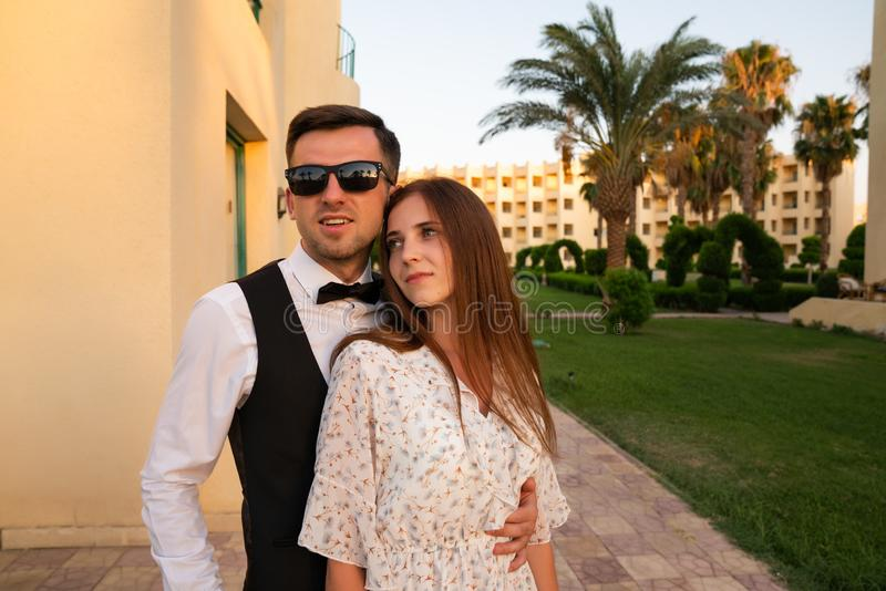 Young attractive man in white shirt and sunglasses hugging his beautiful brunette girlfriend in delicate dress, well royalty free stock image