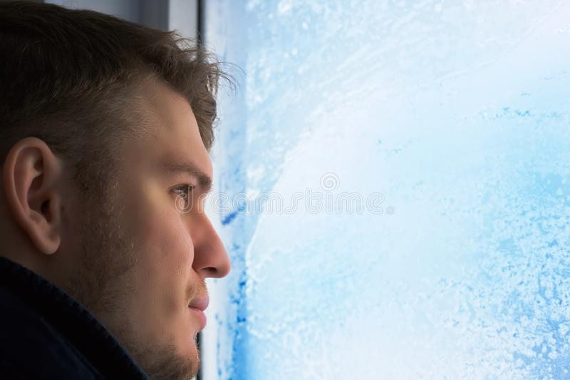 Young attractive man in winter day looks out the window. Glass in hoarfrost and snowflakes. Close-up portrait in natural stock photo