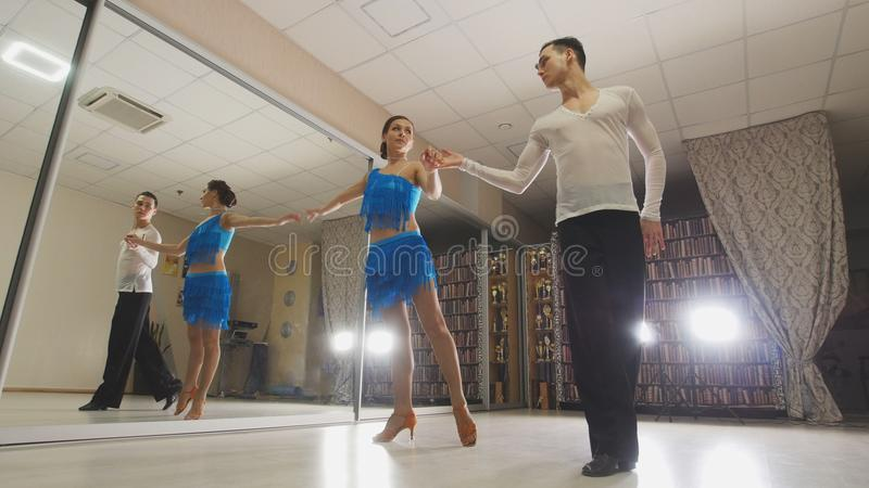 Young attractive man and woman dancing Latin American dance in costumes in the Studio, slow motion, close up, in action. Young attractive men and women dancing stock photography