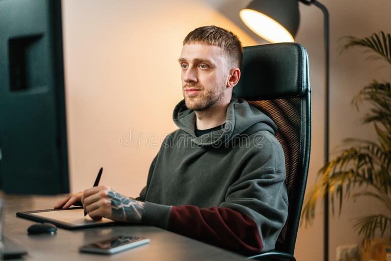Young attractive man working on Graphics tablet. Modern working place of designer, painter, photographer. Young attractive man working on Graphics tablet stock photography