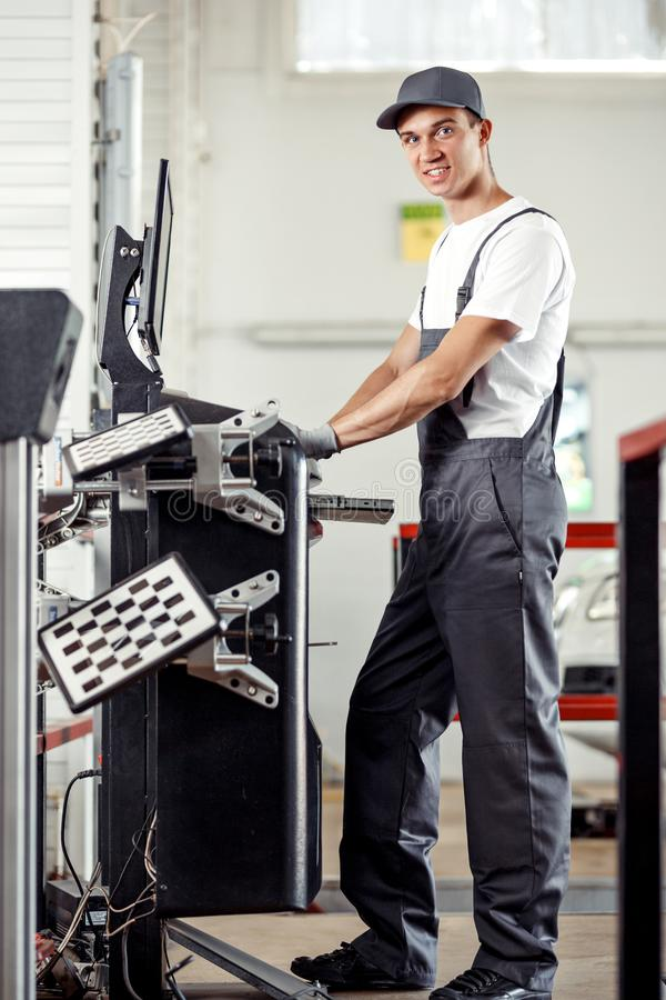 A young and attractive mechanic is smiling while working at a car service using a computer royalty free stock image
