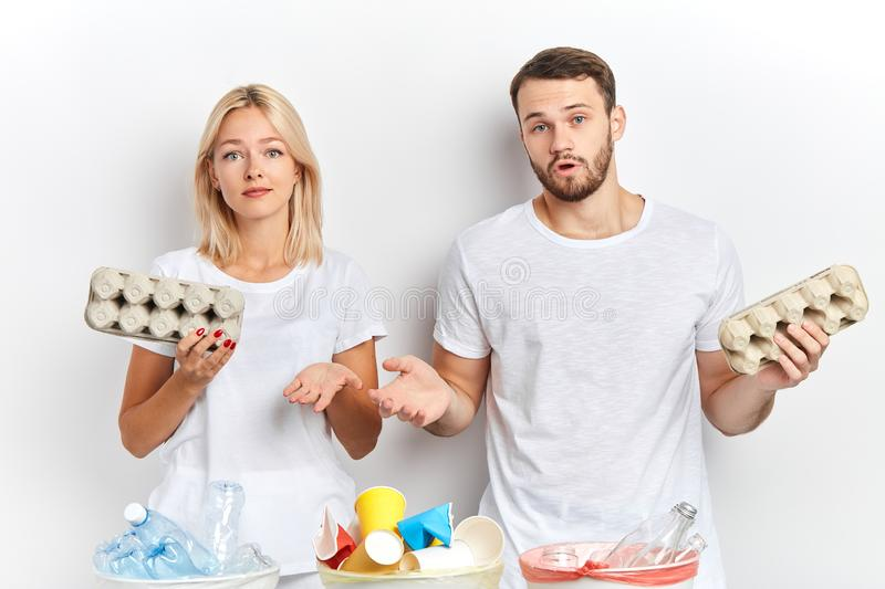 Young attractive man and woman shrugging their shoulders. Young attractive men and women shrugging their shoulders, being surprised with rude people`s behavior stock image