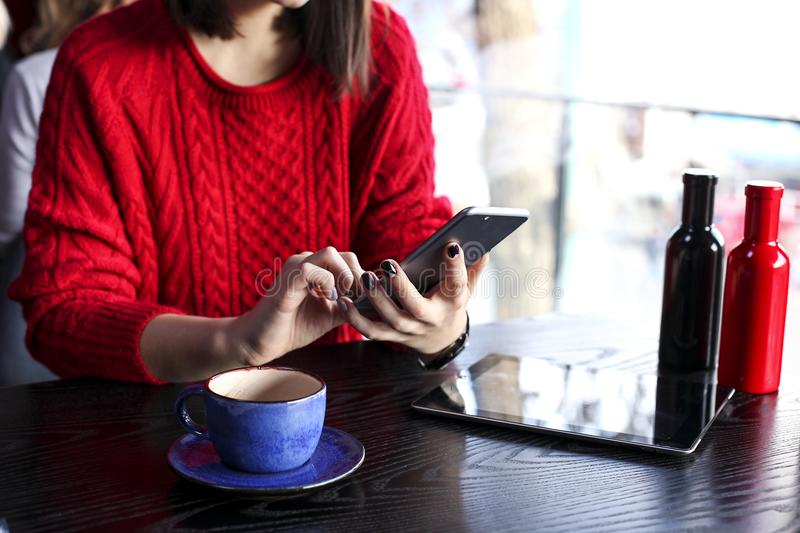 Happy young woman drinking cappuccino, latte, macchiato, tea, using tablet computer and talking on the phone in a coffee shop / ba royalty free stock image