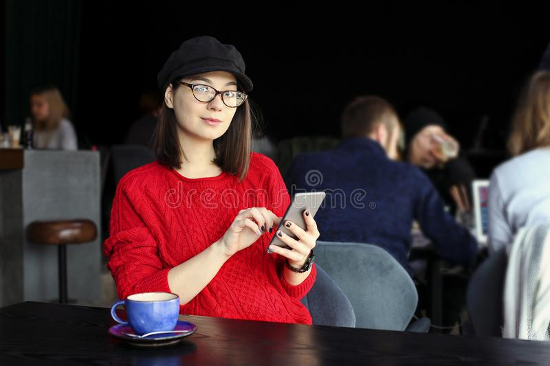 Happy young woman drinking cappuccino, latte, macchiato, tea, using tablet computer and talking on the phone in a coffee shop / ba royalty free stock photo