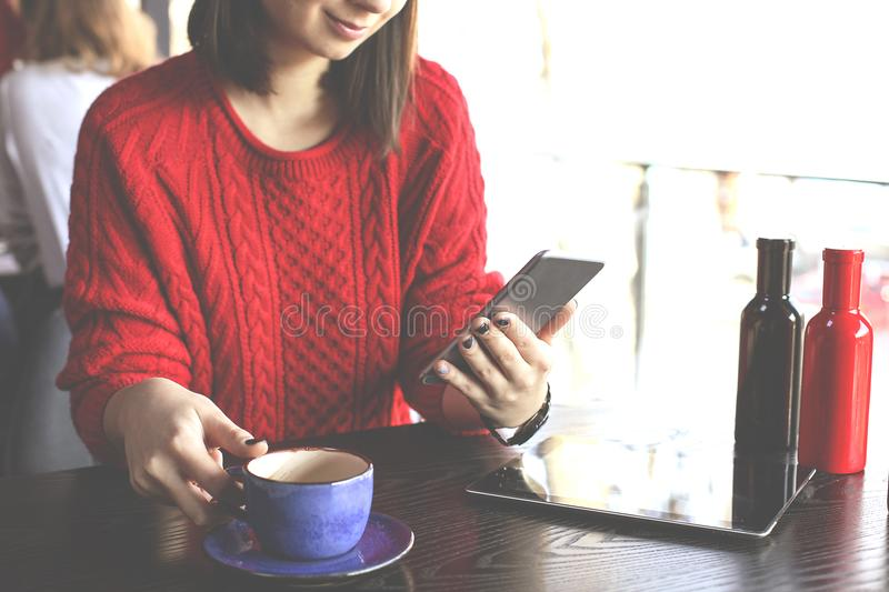 Happy young woman drinking cappuccino, latte, macchiato, tea, using tablet computer and talking on the phone in a coffee shop / ba stock photo