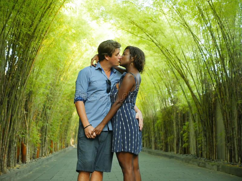 Young attractive mixed ethnicity couple kissing outdoors with attractive black afro American woman and handsome Caucasian stock photo