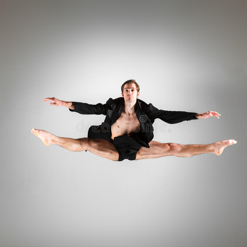 The young attractive modern ballet dancer jumping. The young attractive modern ballet dancer in black jacket jumping over gray background royalty free stock photography