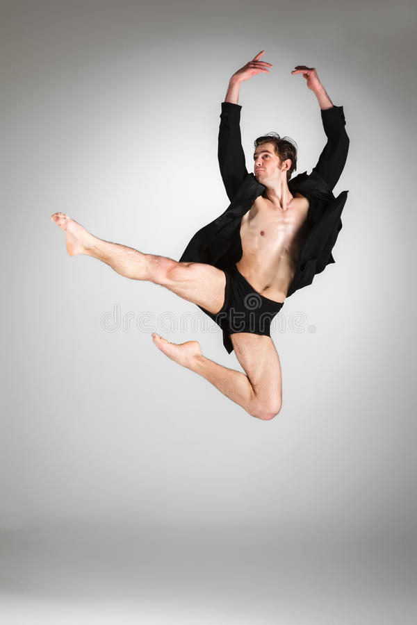 The young attractive modern ballet dancer jumping. The young attractive modern ballet dancer in black jacket jumping over gray background stock photos