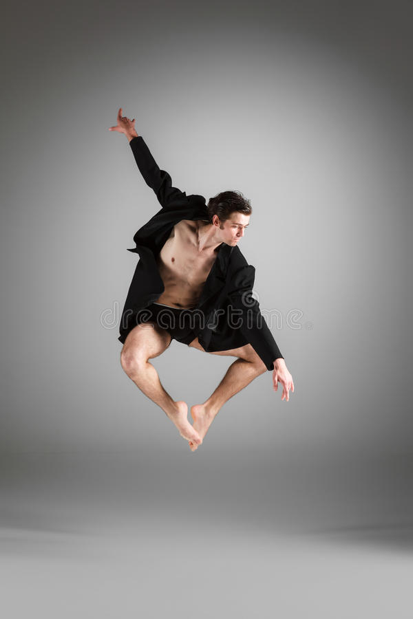 The young attractive modern ballet dancer jumping. The young attractive modern ballet dancer in black jacket jumping over gray background royalty free stock images