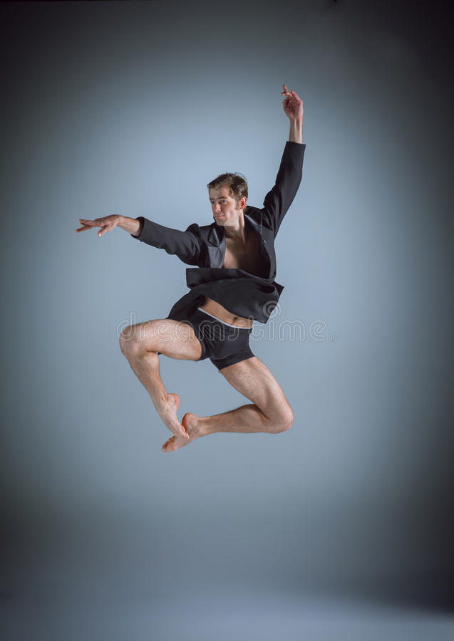 The young attractive modern ballet dancer jumping. Over gray background royalty free stock photos
