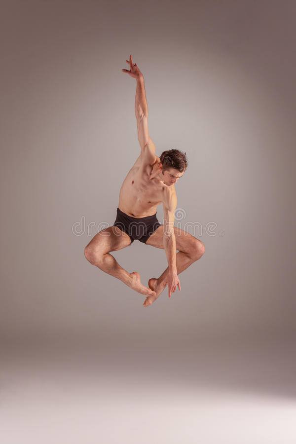 The young attractive modern ballet dancer jumping. Over gray background stock images