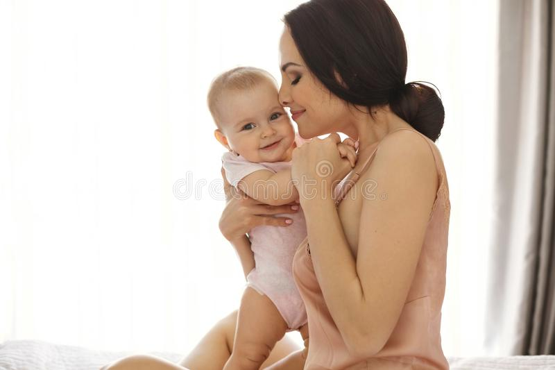 Young attractive mom in sleepwear smiling hugging kissing her baby sitting in bed over window. Closed eyes. royalty free stock photography