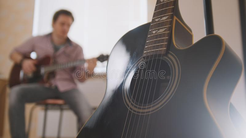 Young attractive musician composes music on the guitar and plays, other musical instrument in the foreground, blurred stock photography