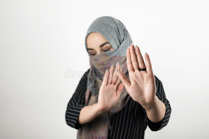 Young attractive Muslim student wearing turban hijab headscarf saying no to war and violence isolated white background stock photography