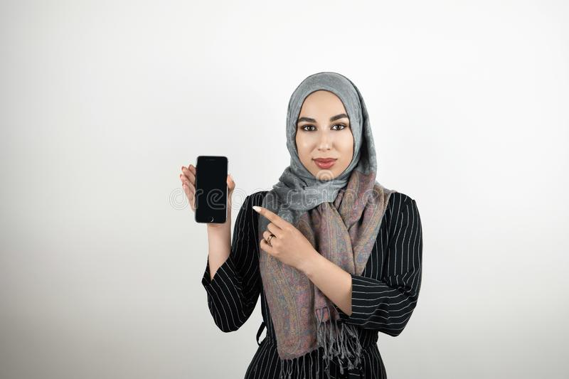 Young attractive Muslim student wearing turban hijab headscarf showing and pointing at smartphone with her finger stock photography