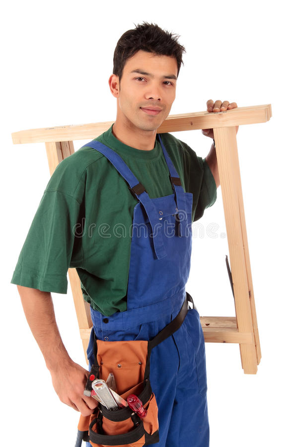 Young attractive Nepalese carpenter. Portrait of young attractive Nepalese carpenter wearing a blue overall, tool belt and a workbench on shoulder . Studio shot stock photos