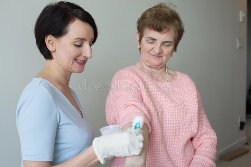 Young attractive nurse medical exam retired woman royalty free stock photo
