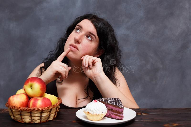 Young attractive overweight woman choosing between healthy food. S and sweets, copy space. Dieting, healthy food, weight losing, well-being royalty free stock photos