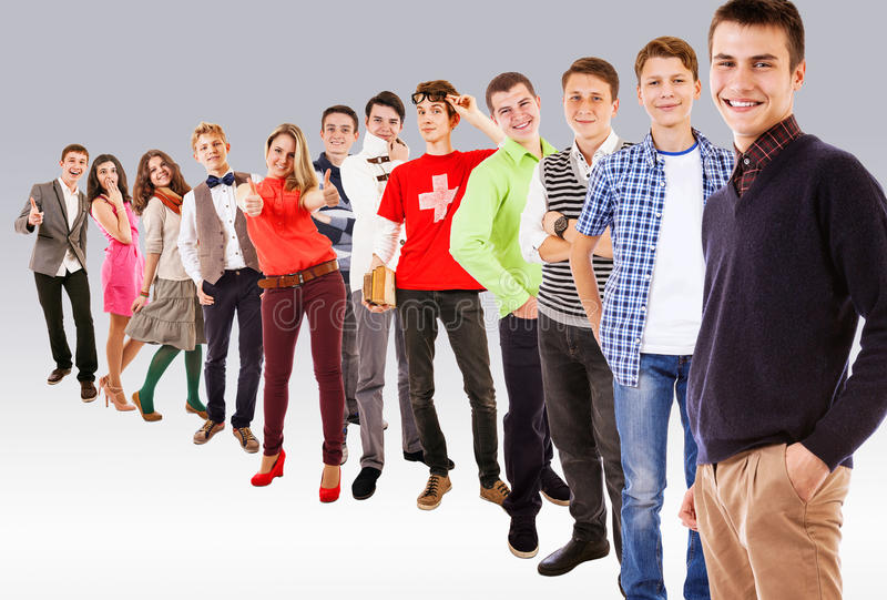Young attractive people standing in rank. Happy young attractive people standing in rank royalty free stock image