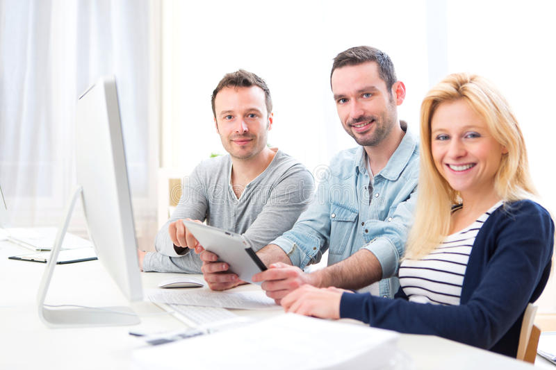 Young attractive people working together at the office. View of a Young attractive people working together at the office royalty free stock photography