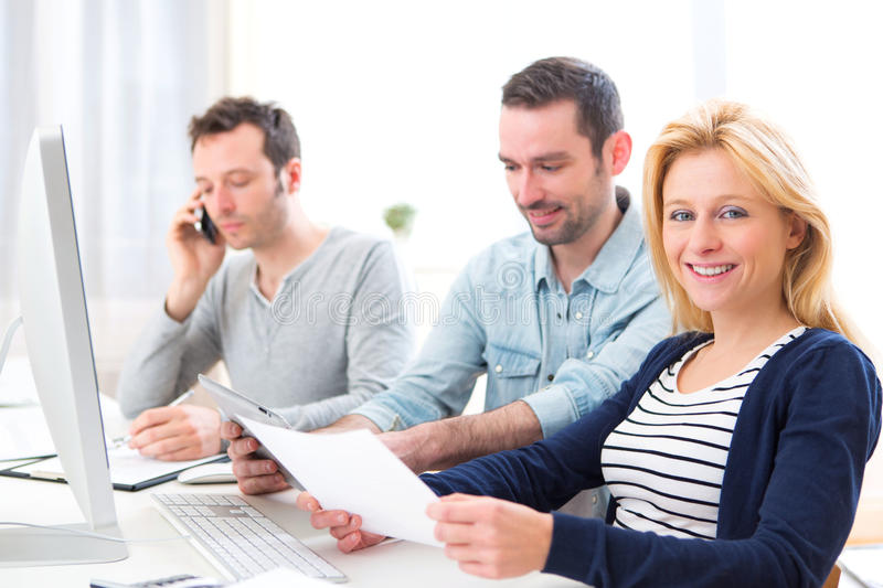 Young attractive people working together at the office. View of a Young attractive people working together at the office stock image