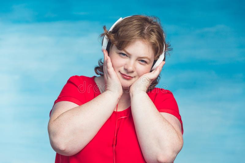 Young attractive plump woman with red hair listening to music with pleasure headphones royalty free stock images