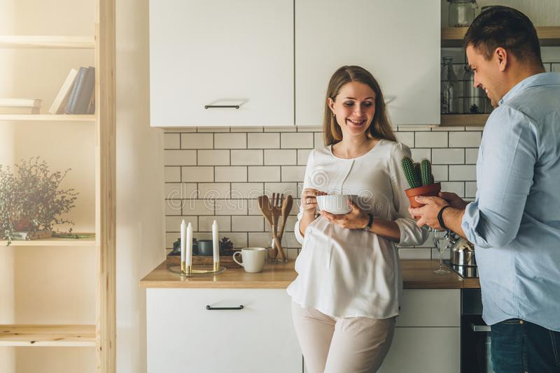 Young attractive pregnant woman is standing in kitchen, leaning on table, holding bowl in her hands. Man stands nearby stock images
