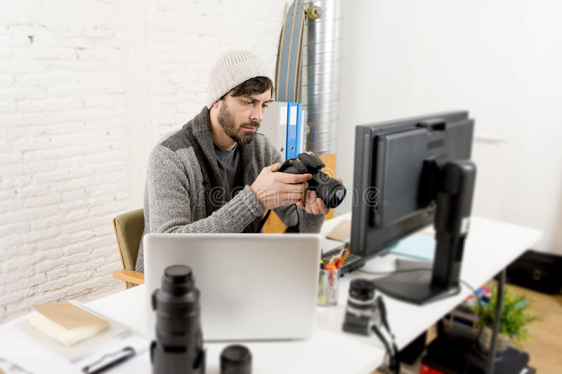 Young attractive press photographer holding photographic camera viewing his work on editor office desk. With laptop and computer monitor and photo lenses and royalty free stock images