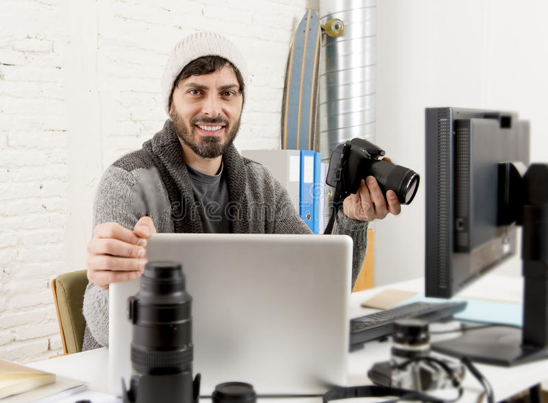 Young attractive press photographer holding photographic camera viewing his work on editor office desk. With laptop and computer monitor and photo lenses and royalty free stock photos