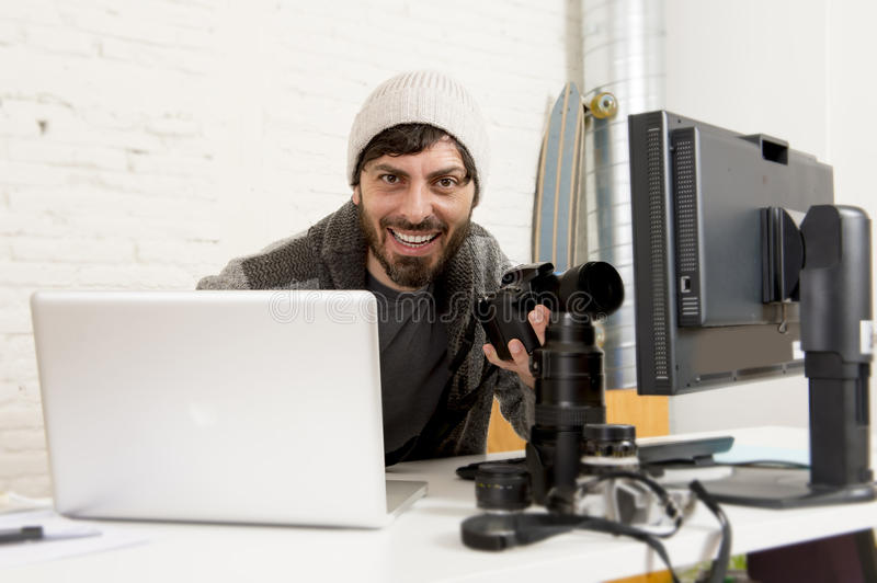Young attractive press photographer holding photographic camera viewing his work on editor office desk. With laptop and computer monitor and photo lenses and royalty free stock photo