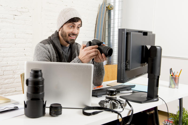 Young attractive press photographer holding photographic camera viewing his work on editor office desk. With laptop and computer monitor and photo lenses and royalty free stock photography