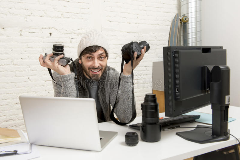 Young attractive press photographer holding photographic camera viewing his work on editor office desk. With laptop and computer monitor and photo lenses and stock photography