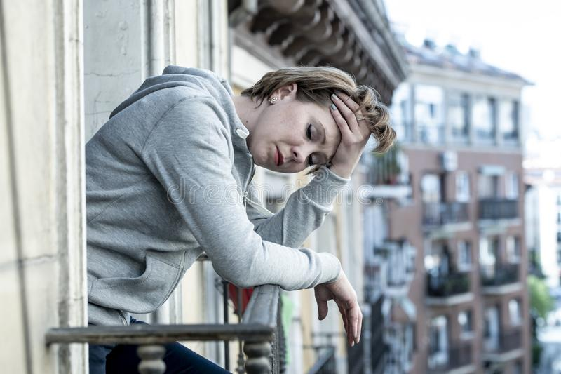 Young attractive woman looking lost and desperate suffering from depression on home balcony stock photo