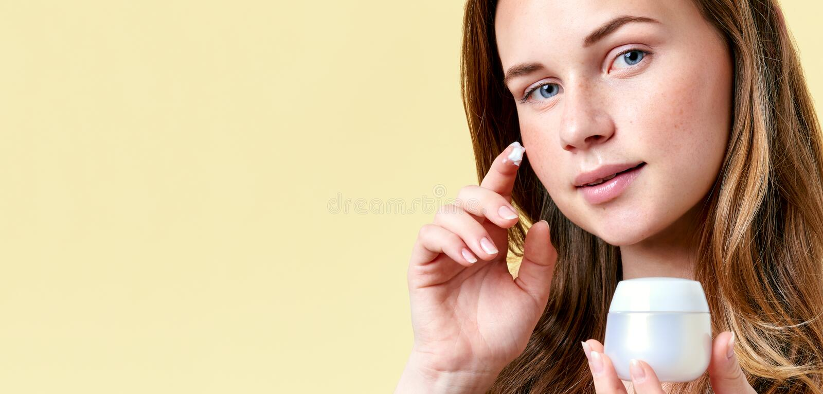 Young attractive redhead woman applying face cream, holding white cream bottle and looking into camera. stock photos