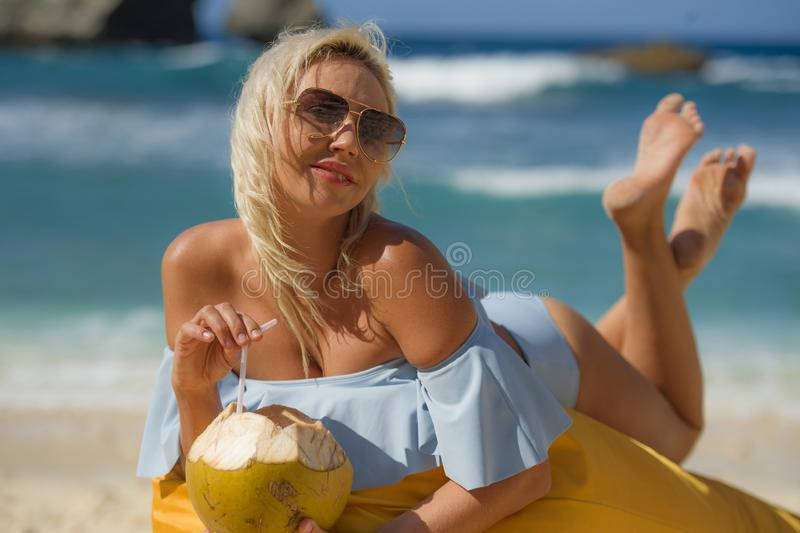 Young attractive and relaxed blond woman in bikini lying on beanbag hammock at tropical paradise beach drinking coconut water royalty free stock image