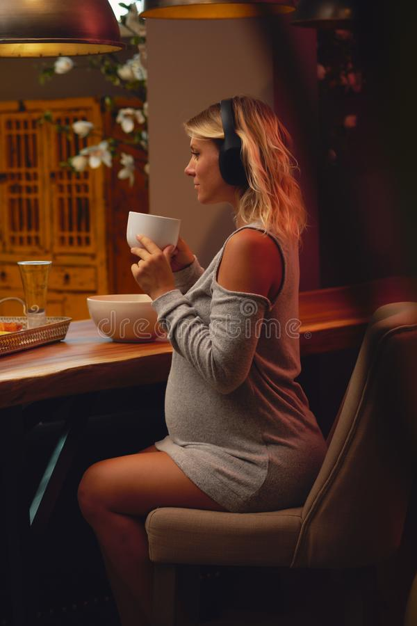 Pregnant woman drinking a tea and listenig music at home. Young attractive relaxed pregnant woman drinking tea and enjoying listening music in headphones royalty free stock photo