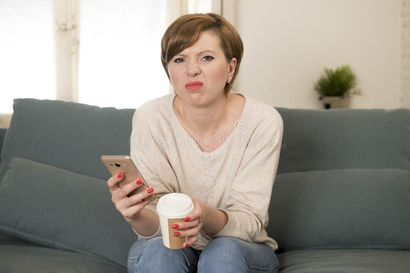 Young attractive 30s red hair woman upset bored and moody using internet app on mobile phone sitting at home sofa couch in annoyed. Face expression royalty free stock photography