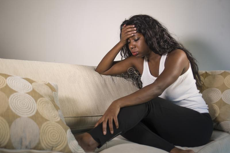Young attractive and sad black African American woman sitting depressed at home sofa couch feeling anxious and frustrated sufferin. G depression problem and royalty free stock photo
