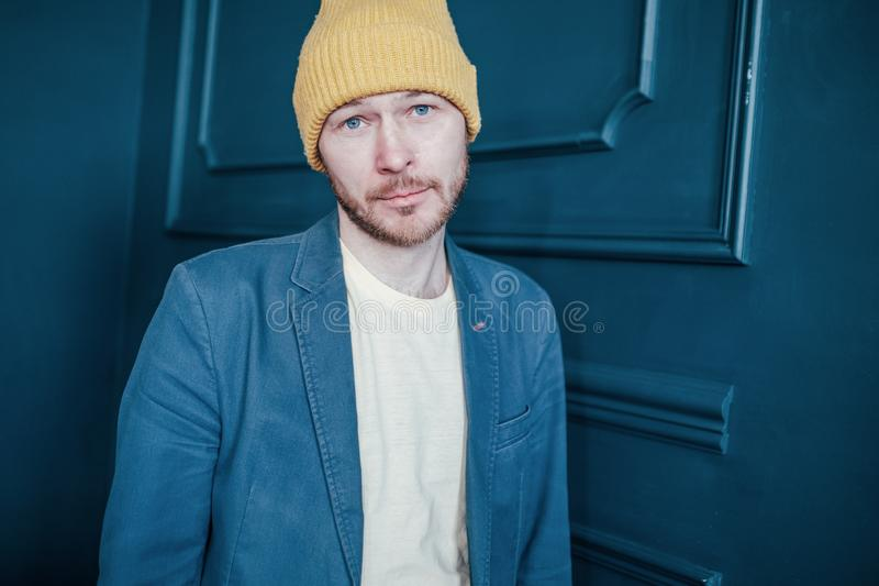 Young attractive sad man infantile loser hipster in the yellow hat on blue background. The Young attractive sad man infantile loser hipster in the yellow hat on royalty free stock images