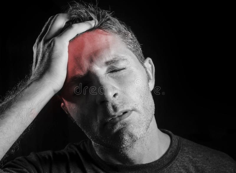 Young attractive and sad man suffering headache with hand on his tempo head in stress looking desperate and sick isolated black a. Nd white portrait with front royalty free stock image