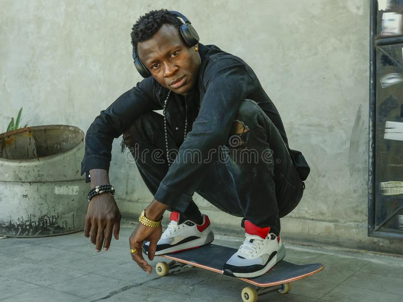 Young attractive and serious black African American man squatting on skate board at grunge street corner looking cool posing in. Urban lifestyle portrait of royalty free stock photos