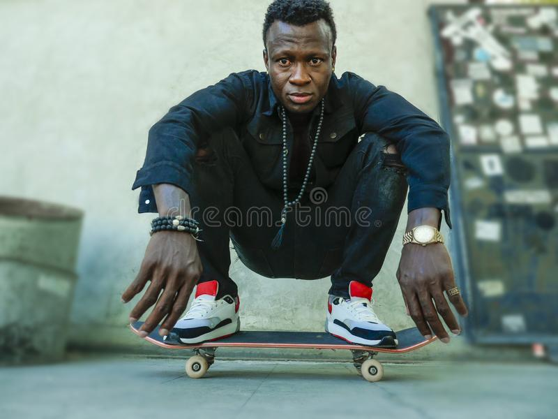 Young attractive and serious black afro American man squatting on skate board at grunge street corner looking cool posing in. Urban lifestyle portrait of young stock photo